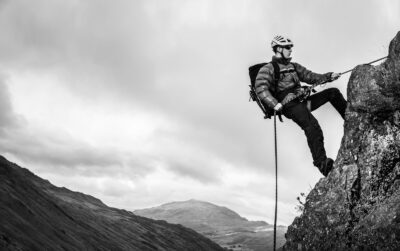 COMMERCIAL PHOTOGRAPHER - A black and white photograph of a model abseiling off the side of a cliff-top